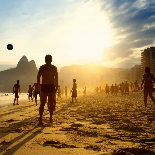Rio de Janeiro beach football silhouettes of Brazilians playing keepy uppy altinho soccer on the sunset shore at Posto Nove Ipanema Beach / Photo credits: Lazyllama / 2015 / Source: depositphotos.com, ©2019